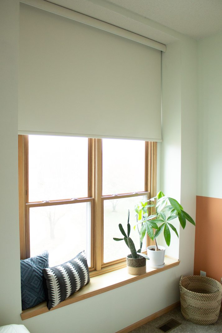 large arched window with wood trim covered with blackout Levolor roller shade from Blinds.com