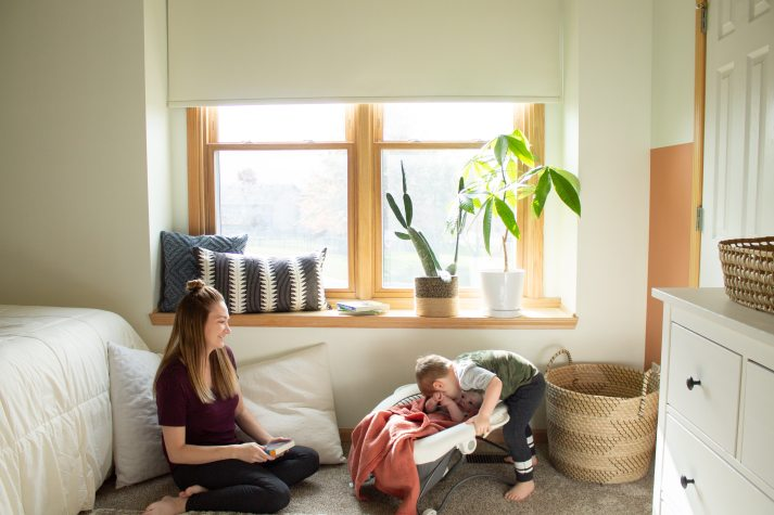 Mom and two kids playing in front of window sill and large window with minimalist roller shades.