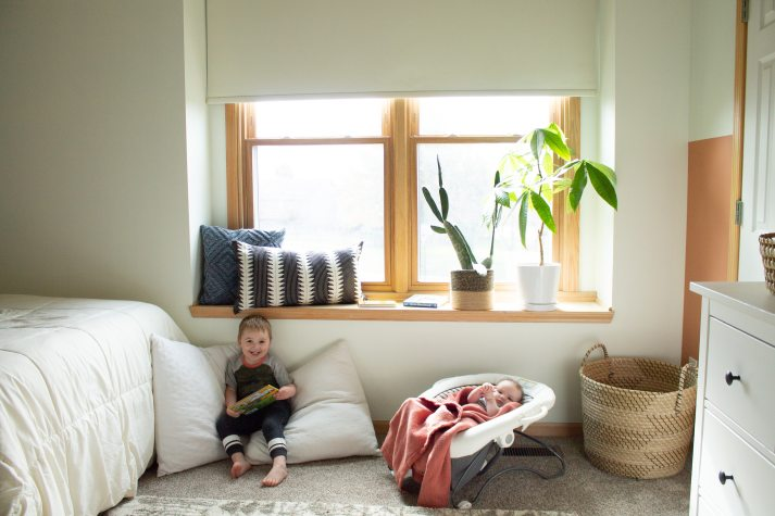 toddler and baby sitting on floor of nursery under large window covered with cordless roller shades