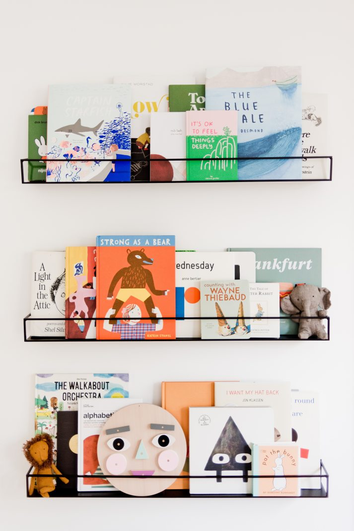 kids bedroom wall with picture ledge shelves holding colorful children's books.
