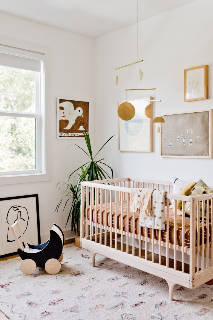 modern nursery with blonde wood crib, brass mobile and white roller shade.