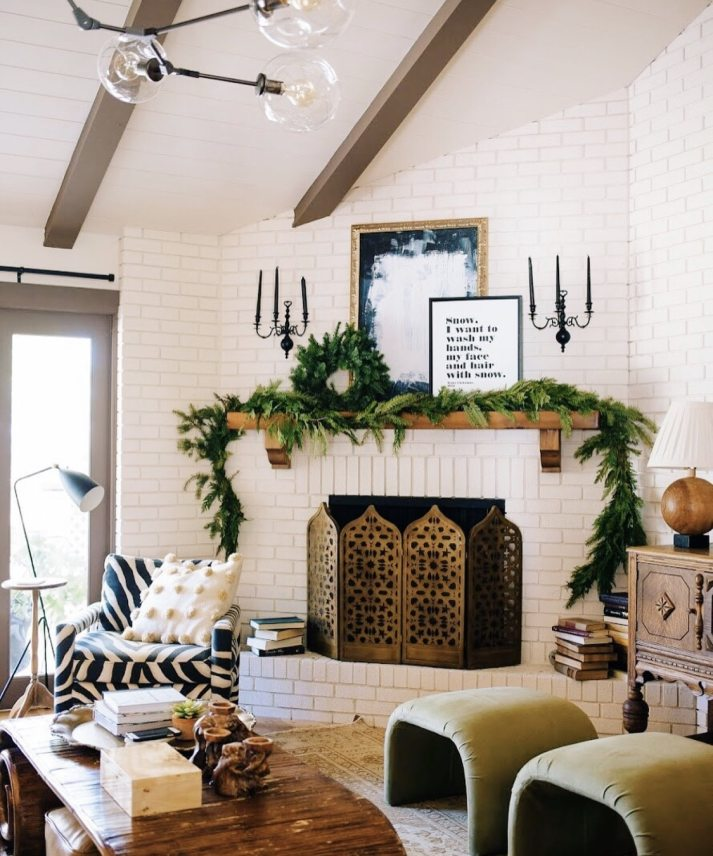 eclectic living room decorated for christmas with plain garland and wreath on mantle