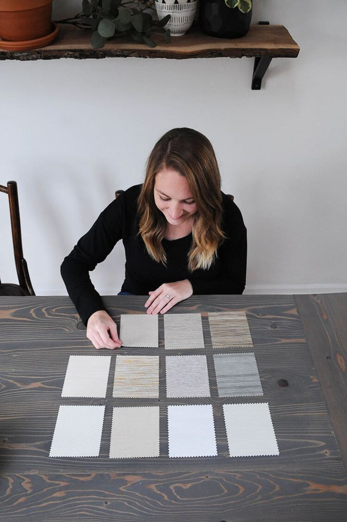 woman looking at fabric samples for Blinds.com roller shades at dining table