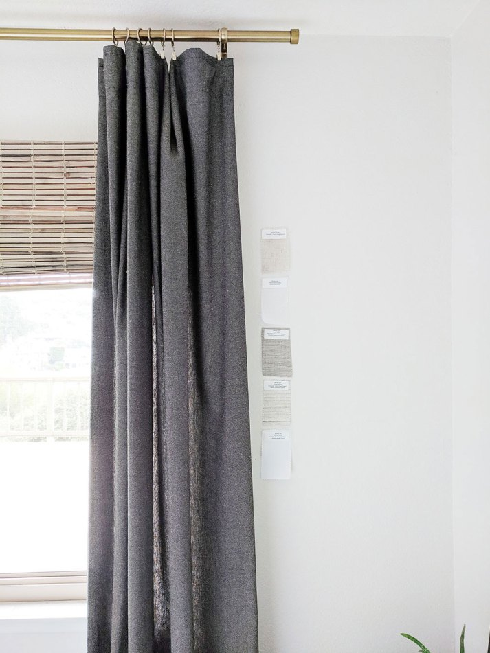 closeup of window treatment fabric samples taped next to dark grey curtains