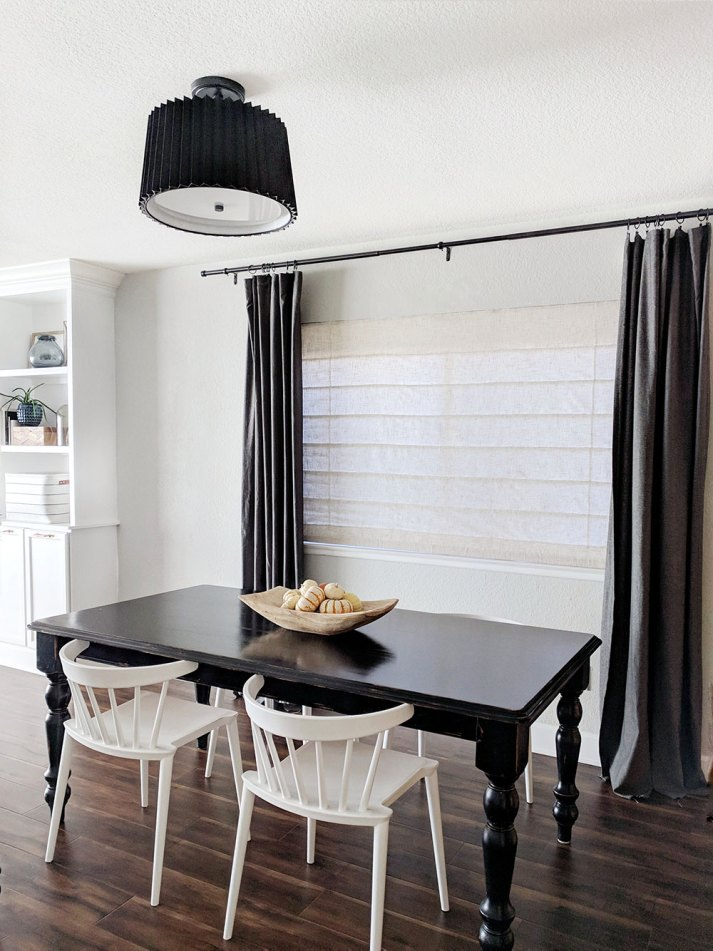 dining table in front of large window with off white roman shades and dark grey curtains