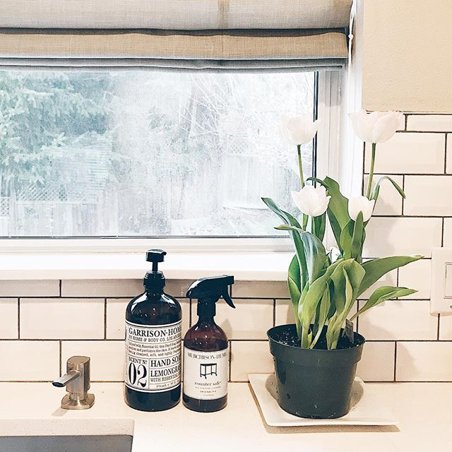 windowsill behind sink with pretty hand soap, tulips in pot and greige roman shades on window