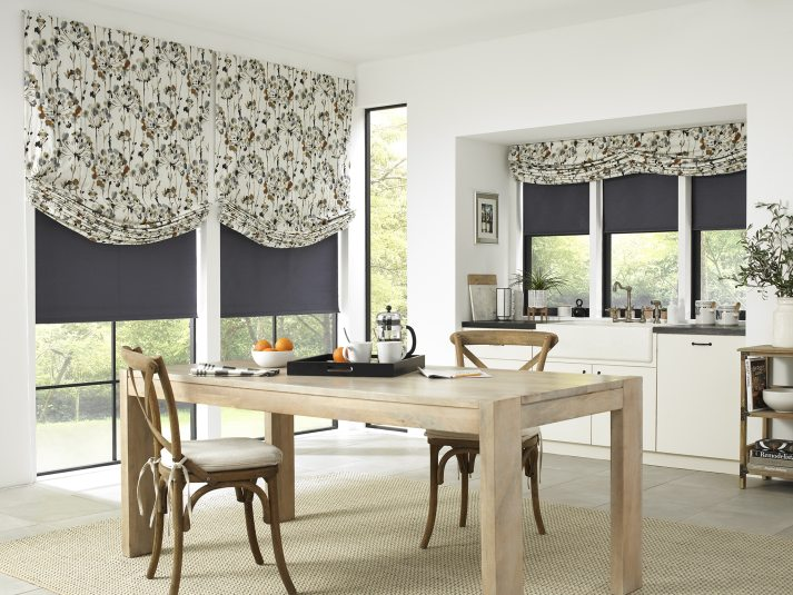 modern farmhouse kitchen with large windows covered with blackout roller shades and floral roman shades with swoop relaxed fold