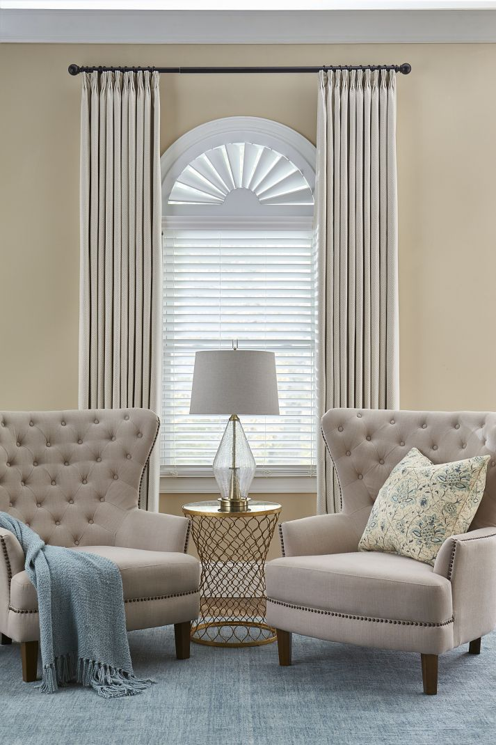 Arched window with white blinds and beige curtains