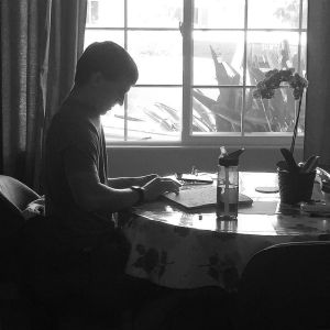 Black and White photo of Eric silhouetted in a bright window, sitting at a table reading a Braille book.