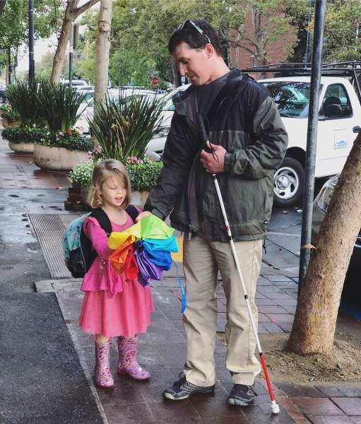 A photo of me and my daughter walking on a sidewalk. I am carrying my white cane and we both have umbrellas, even though the rain has stopped.