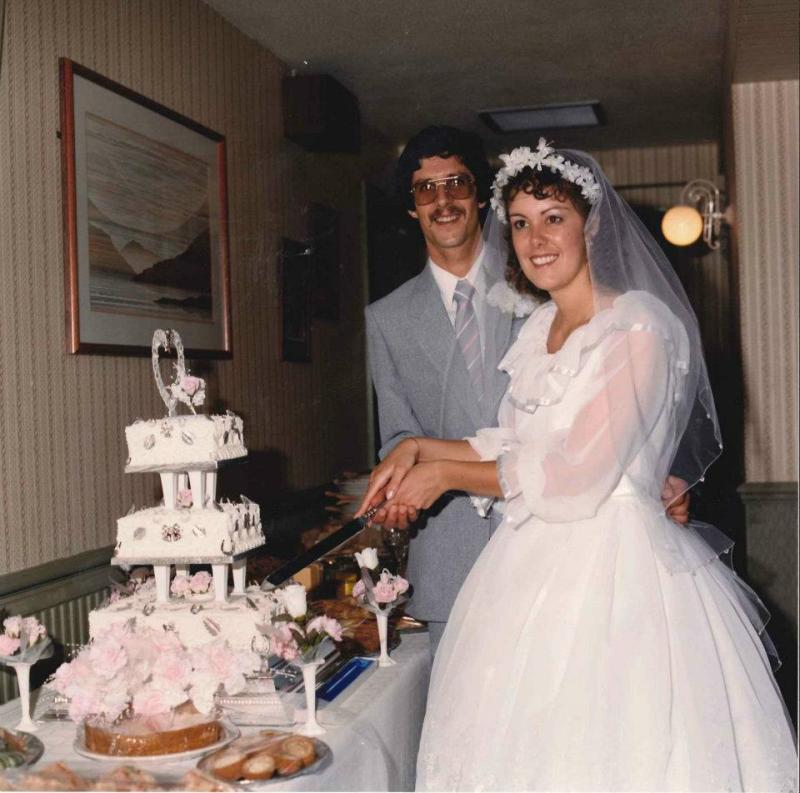 Wedding photo - Tim, dark haired weating pale grey suit and Tracey - dark, wavy haired wearing white wedding dress and veil. They are holding a large knife - about to cut the bottom tier of a triditional 3 tier wedding cake