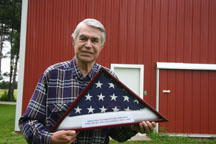 "World War II orphan Ferenz ""Fritz"" Whitman of Riga displays the flag he received when he became a U.S. citizen."