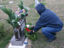Lloyd Pitney puts a wreath on the grave of his cousin, veteran  Staff Sgt. Bryan Pitney, a Deerfield, Michigan, native. (Copyright 2015, River Raisin Publications, Inc. All rights reserved)