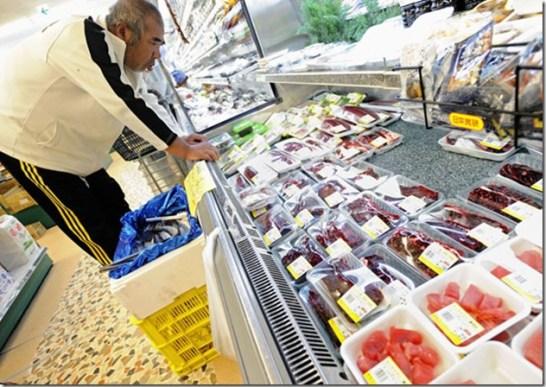 Un homme examinant viande de dauphin et autres sashimi dans un supermarché de Taiji - Photo de The Guardian