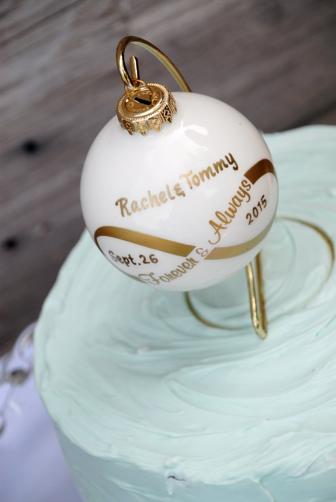 Bronner's personalized white and gold forever and always ornaments hung from a gold ornament stand as a wedding cake topper
