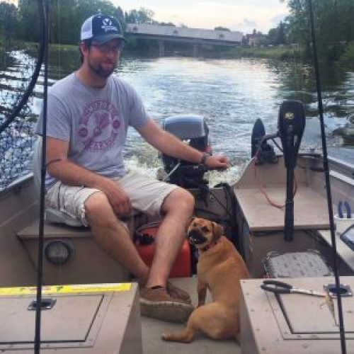 Shannon's husband Hegi in the fishing boat on the river with smiling Penny