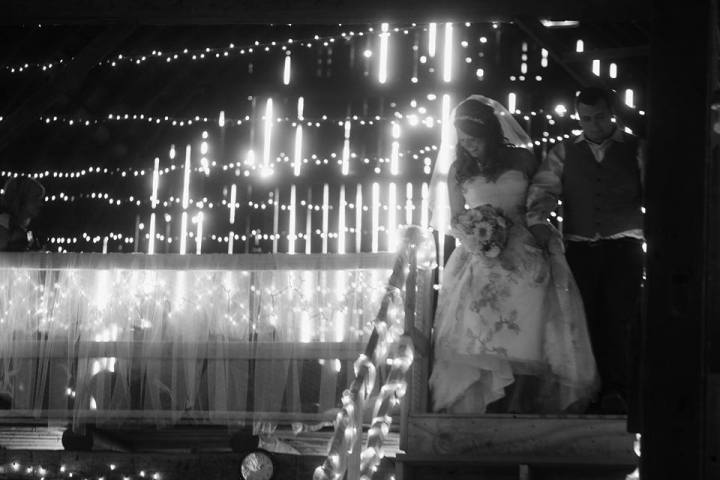 black and white wedding photo featuring bride and groom with multitude of string and rope white lights decorating the venue