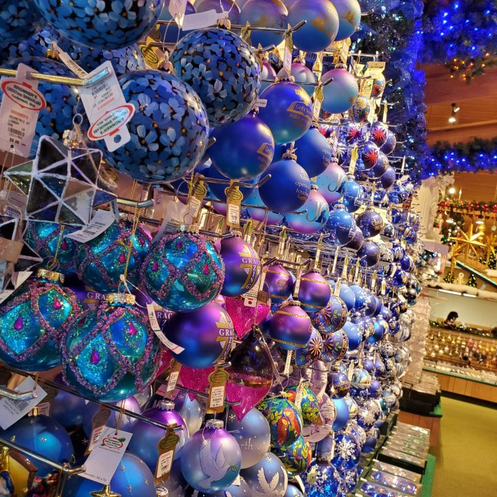 Christmas trends 2020 feature a closeup of blue glass ornaments lining a wall with blue lighted evergreen garland overhead.