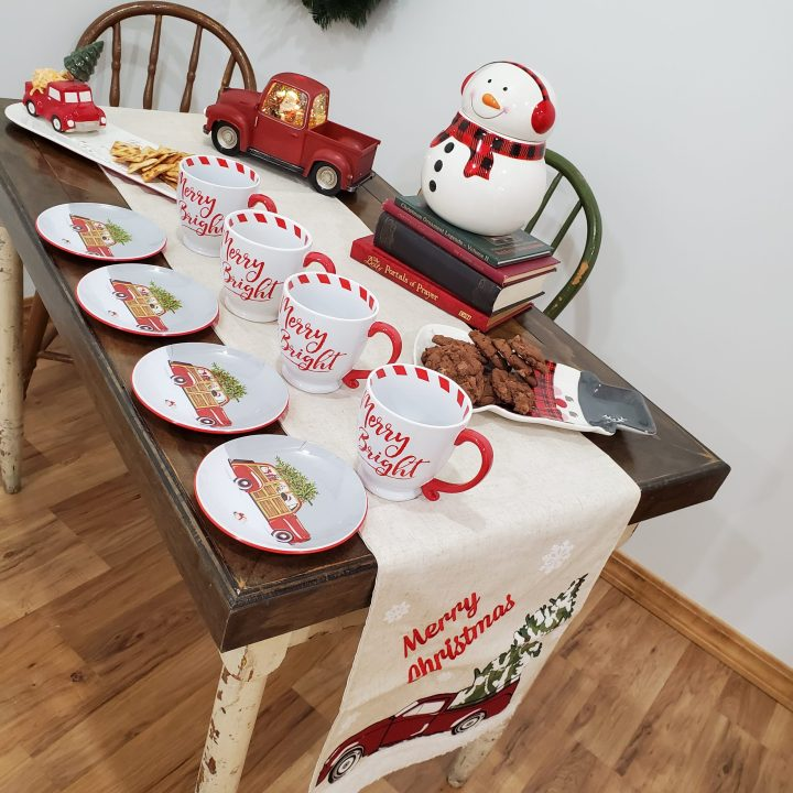 Table set with Merry Christmas and red vintage pickup truck table runner, small melamine plates with antique car topped with Christmas tree, Merry & Bright mugs, snowman cookie plate and cookie jar, pickup truck cheese and crackers tray and pickup glitter-globe Santa cab