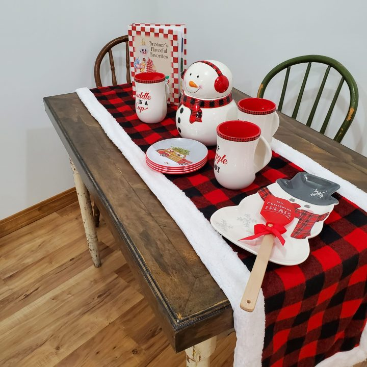 "Christmas table decorated with buffalo plaid table runner, ""Bronner's Flavorful Favorites"" cookbook, Christmas mugs, holiday melamine plates, a snowman cookie jar, and a Christmas spatula on a snowman platter. Perfect for Christmas trends 2020."