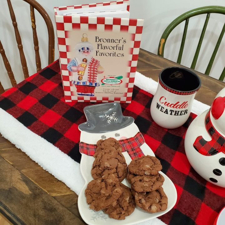 "Closeup of half of tabletop with buffalo plaid table runner, ""Bronner's Flavorful Favorites"" cookbook, Christmas mug, and snowman platter with seven chocolate chocolate chip cookies on the platter made from the recipe in ""Bronner's Flavorful Favorites"" cookbook."