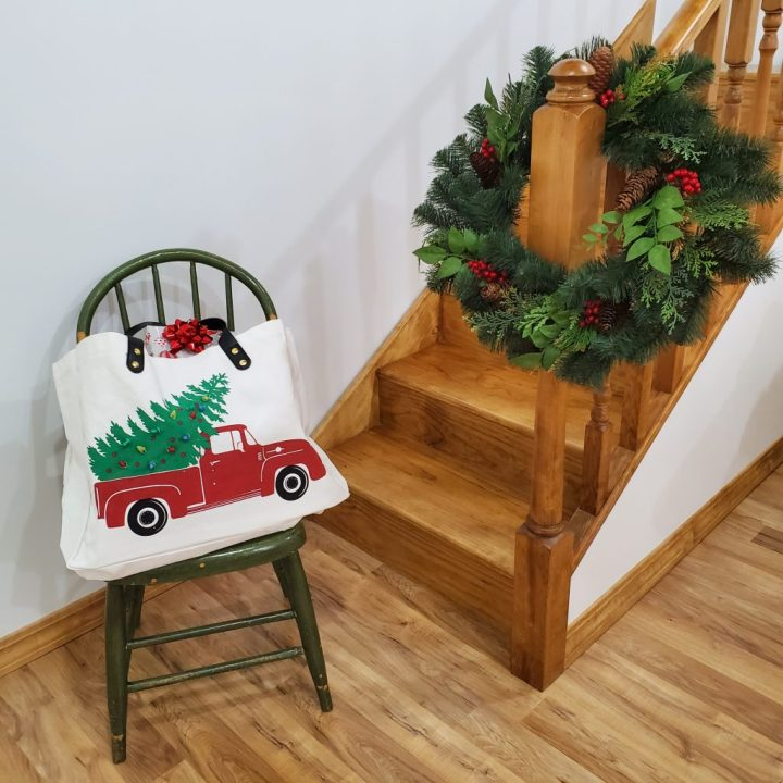 Large canvas tote with vintage red pickup truck art with battery-lighted tree in the back of the truck. Tote is sitting on green chair next to stairway with Christmas wreath on bottom spindle of stairway