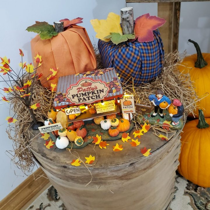 Closeup of Patty's Pumpkin Patch and an orange along with an orange/navy/sky blue plaid toilet paper roll pumpkin for decorating for fall with Department 56.