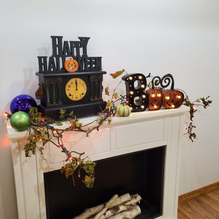 "Decorating tip for Halloween to top a white fireplace mantel with  Krypton green and purple shatterproof ornaments, a black mantel clock set to midnight and topped with a Happy Halloween self-standing tabletop piece, a green gourd next to the clock and then a metal ""Boo"" lighted marquee sign all with a dried grapevine strung with orange LED lights woven through it."