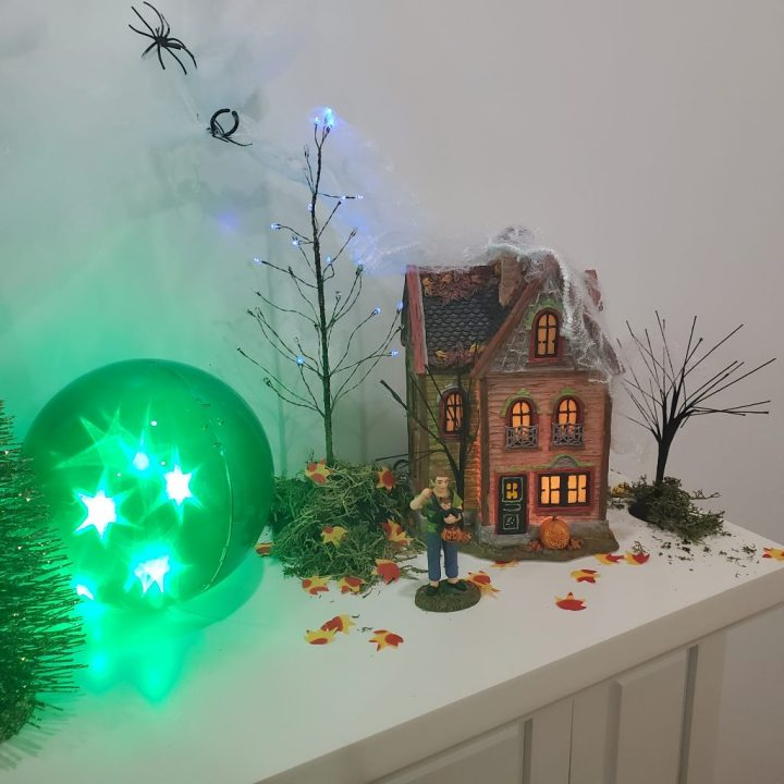 One end of the white fireplace mantel topped with a sphere with green phasing effect and the Department 56 Spider House boxed set and purple twinkle brite tree