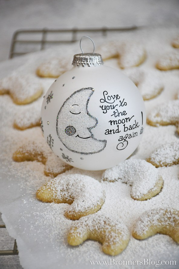 Almond crescent cookies covered with powdered sugar and topped with an ornament.