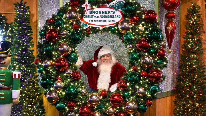 Santa Claus posing behind a large decorated wreath