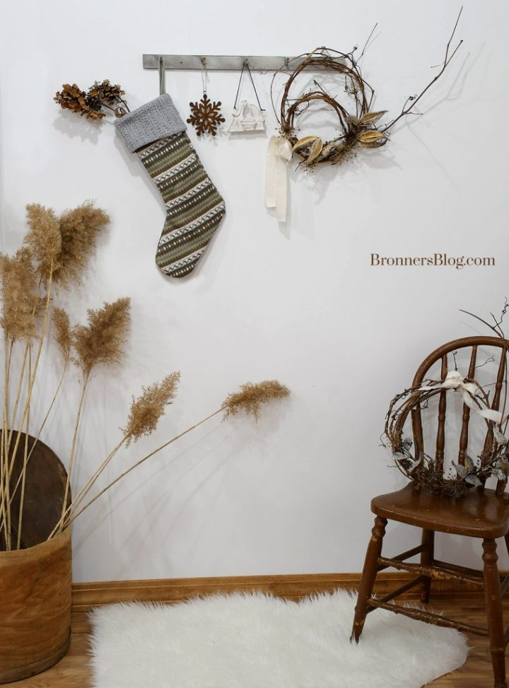 The room features a peg board with natural decor for Christmas flanked by a wooden cheese box filled with wild pampas grass and a brown wooden chair with a grapevine wreath on it.