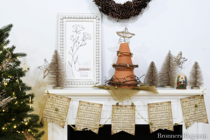 "The white fireplace mantel is topped with the terra cotta tree, silver glitter trees with wire rattan stars, wood ""Be still and know I am God"" wall art, an earthenware Nativity luminary with animals, and is draped with a silver and gold bead garland with vintage-look ""Silent Night"" sheet music for sustainable decorations for Christmas."