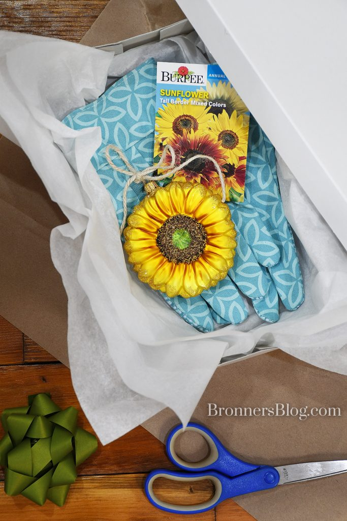 A gift box with white tissue paper in it holds a blue pair of gardening gloves, sunflower seed packet and sunflower glass ornament.