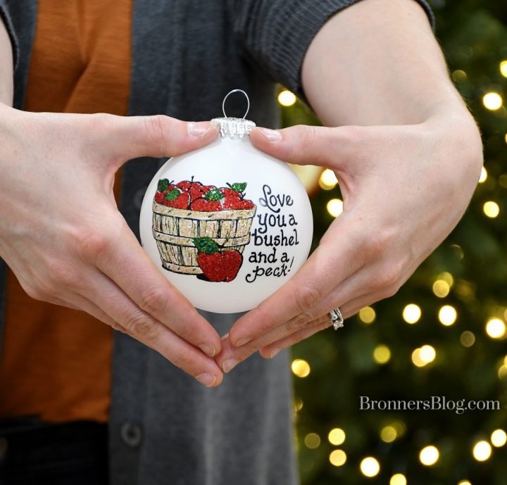 """Heart Gifts glass ornament by Teresa Thibault with a bushel basket of apples and the sentiment, """"Love you a bushel and a peck"""" being held by heart-shaped hands."""
