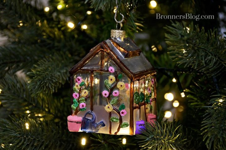 Celebrate great garden tips with this glass greenhouse ornament with pink and yellow flowers, pots and watering cans painted on it as it hangs from a lit Christmas tree.