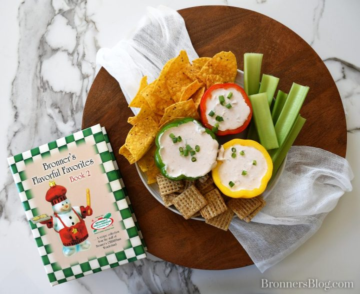 Three Pepper Dip served in colorful pepper bowls and served with tortilla chips, celery and crackers.