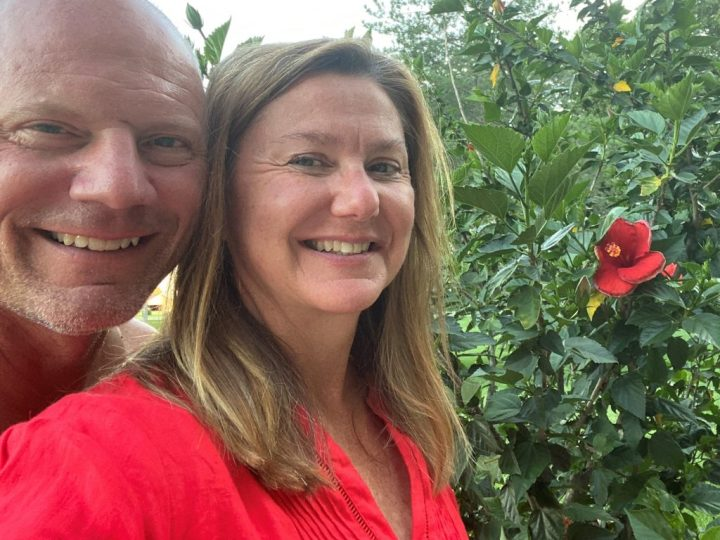 Head and shoulder shot of Chris and Maria next to their hibiscus they've had since they married. Maria completed master gardener training and offers great garden tips.