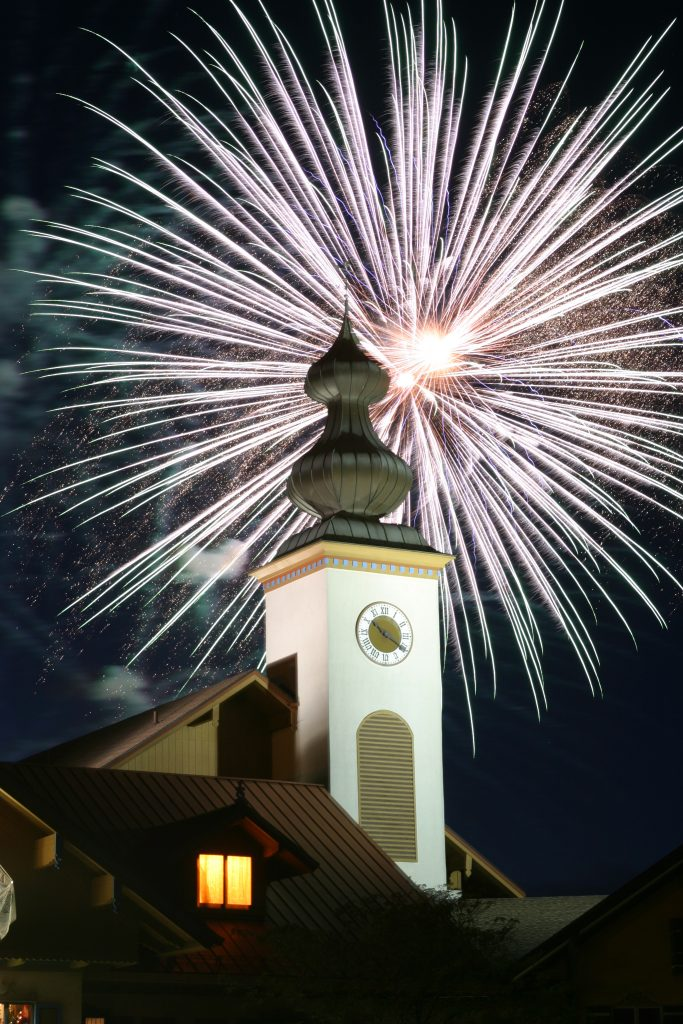 Large, white fireworks explode over clock tower at Bavarian Inn Lodge in Frankenmuth during Fourth of July fireworks
