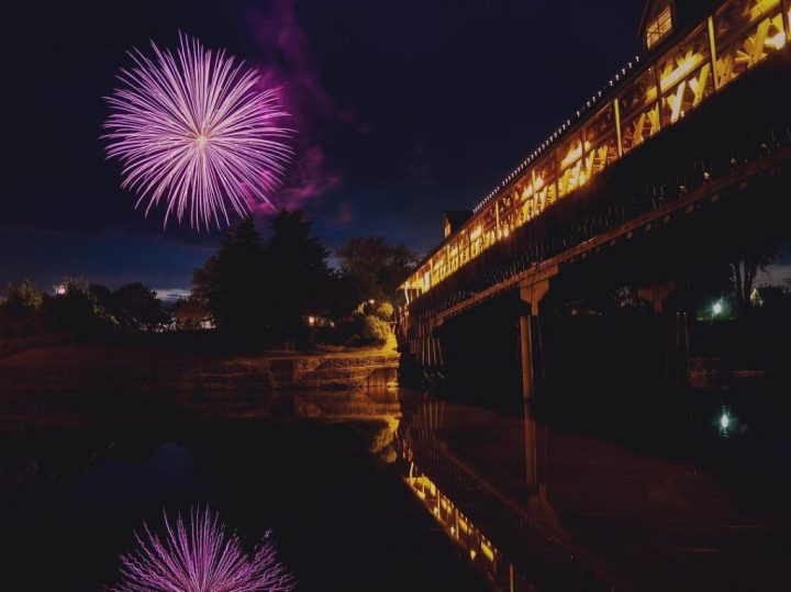 Purple fireworks reflect in river next to the wooden bridge in Frankenmuth during Fourth of July fireworks.