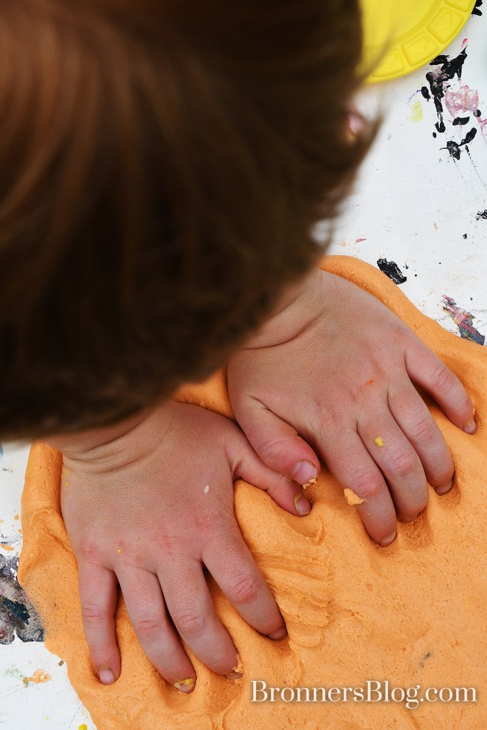 Putting handprints into homemade playdough.