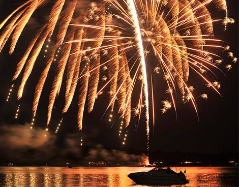 Golden Fourth of July fireworks reflect over the bay in Traverse City, Michigan.