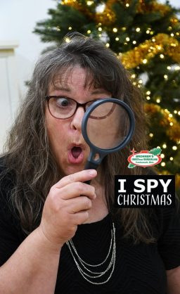 Lady playing I Spy Christmas looking through a magnifying glass with a Christmas tree behind her