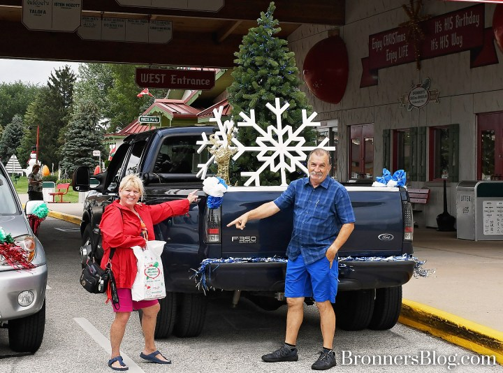 Guests pose next to decorated Christmas cars at Bronner's