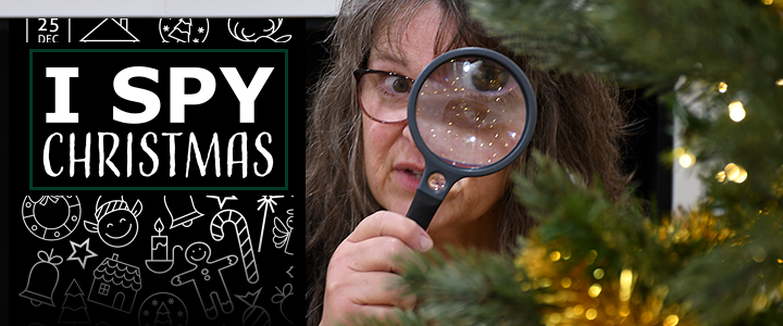 lady playing I Spy Christmas and looking at Christmas tree through magnifying glass
