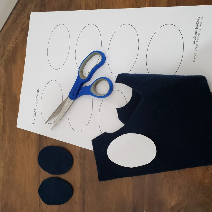 sheet of oval templates, scissors, piece of black felt and oval eyes cut out from black felt