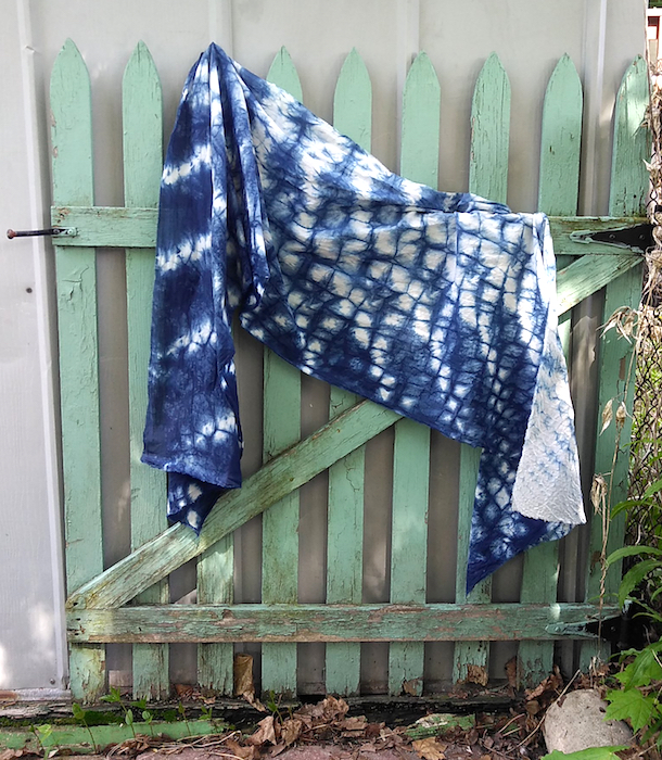 nui shibori indigo scarf draped on green picket fence doris lovadina