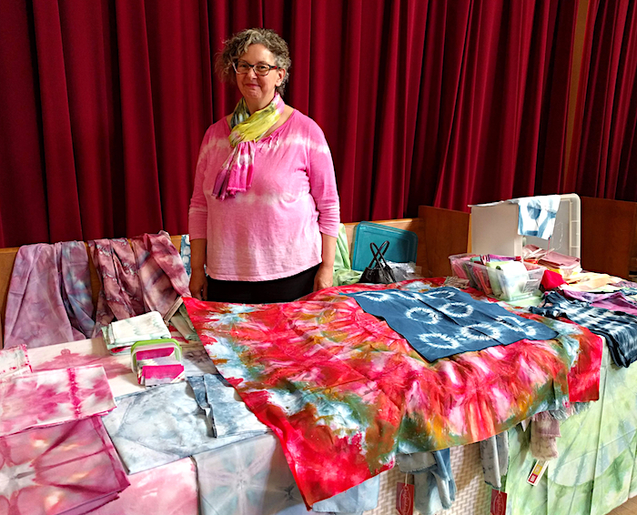 Doris Lovadina-Lee standing behind table covered with hand dyed scarves and fabric at the Toronto Modern Quilt Guild meeting