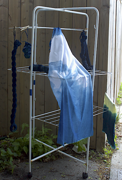 white cotton indigo dyed fabric and yellow wool fabric dyed in indigo hanging from metal stand