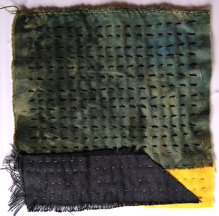 green, black and yellow hand dyed fabric held together with running stitch by doris lovadina-lee